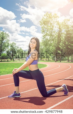 Young adult slim fit girl doing some stretching relaxing exercises on athletic track during hot summer day. - stock photo