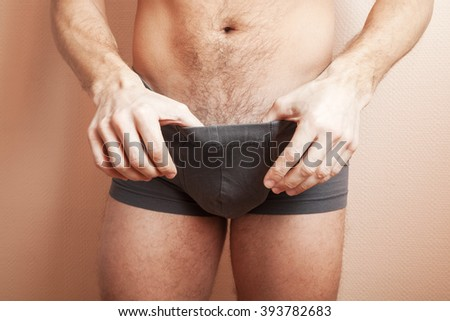 Young adult sporty man pulls gray boxer underpants and looks inside, close-up studio photo with selective focus