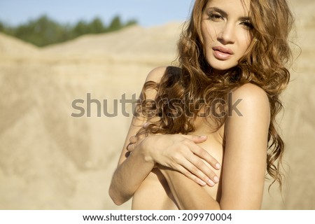 Young adult topless sensuality brunette girl in white jeans over sand background