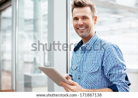 Young adult with a tablet in his hand and smiling into the camera - stock photo