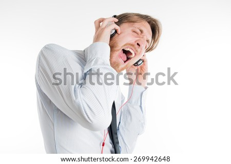 Young adult with headphones screaming and singing - stock photo