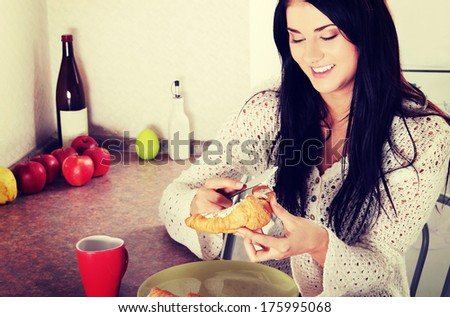 Young Adult Woman Eating Breakfast - stock photo