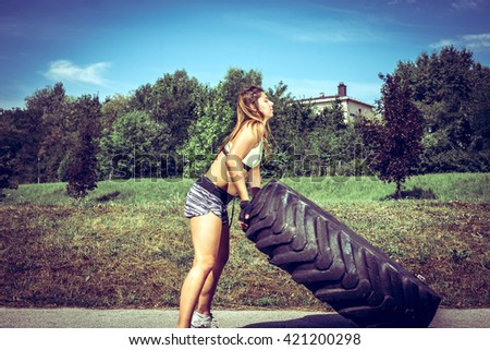 Young adult woman flipping and rolling tire during  exercise outdoor. Toned image. - stock photo