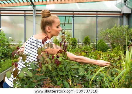 Young adult woman gardening in a greenhouse, planting some flowers