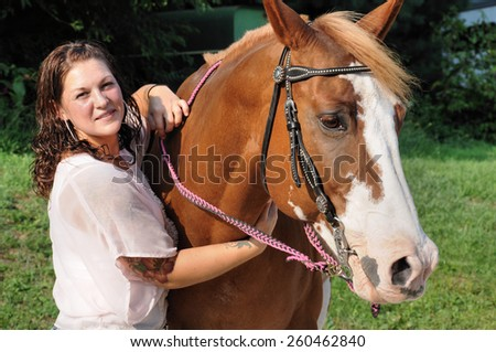 Young adult woman holding her horse - stock photo
