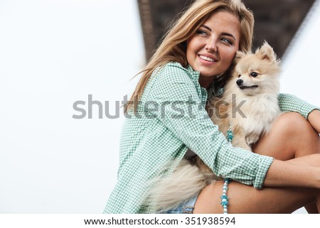 Young adult  woman is holding a dog in her hands - stock photo