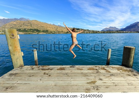 young adult woman jumping in to the lake with joyful - stock photo