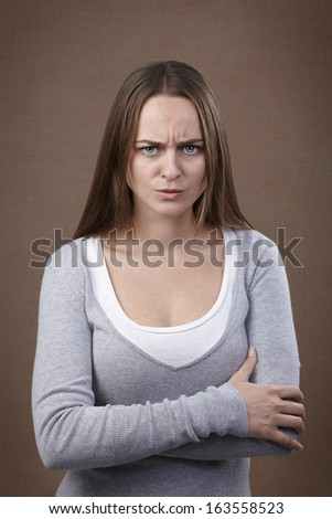 Young adult woman looking at camera displeased and angry