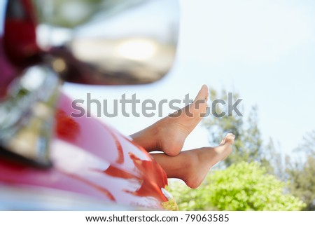 young adult woman relaxing with feet out of convertible red car. Horizontal shape, side view, copy space - stock photo