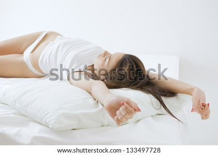 Young adult woman waking up and streching on bed in the morning