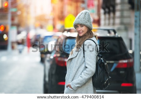 Young adult woman walking on city street wearing hat and jacket with backpack. Winter Cute smiling woman wearing autumn casual street style outfit.