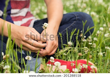 Young adult woman wearing red, white and blue holding clover flower - stock photo