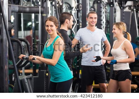 Young adults doing powerlifting on machines in fitness club