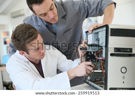 Young adults fixing computer hardware in technology school