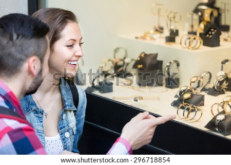 Young adults looking at shopwindows with luxury bracelets, jewelry and watches - stock photo