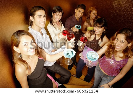Young adults raising drinks to camera