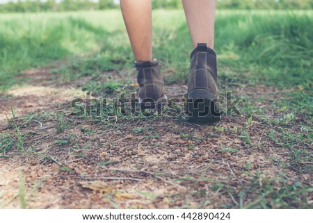 Young adventure woman feet walking on gravel in the countryside.