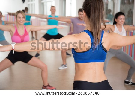 Young aerobics instructor showing exercises during fitness classes - stock photo