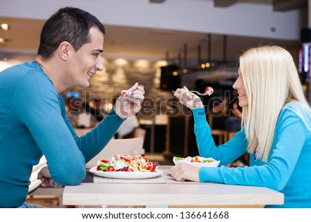 Young affectionate couple together on lunch at restaurant - stock photo