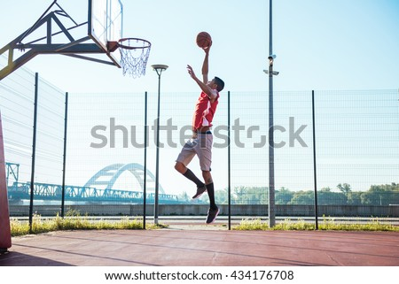 Young african american basketball player scoring a slam dunk. - stock photo
