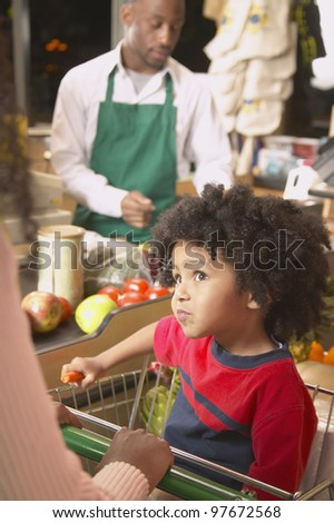 Young African American boy in shopping cart at supermarket checkout - stock photo