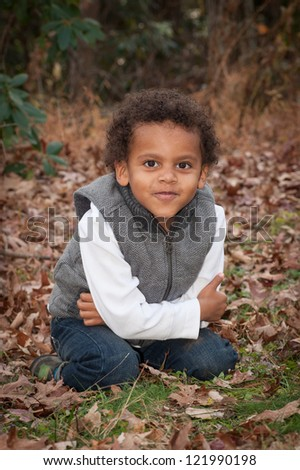 Young african american boy sitting in the leaves on his knees with his arms around himself while looking at the camera.