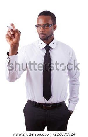 Young African american business man  writing something on glass board with a marker - stock photo