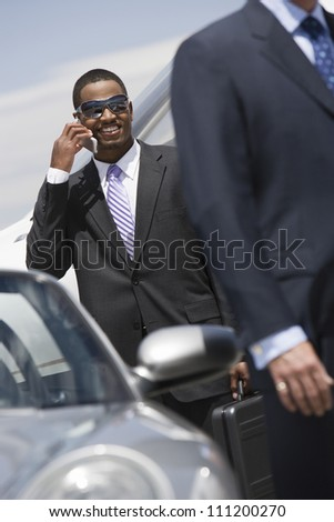 Young African American businessman on a call standing by car at airfield - stock photo