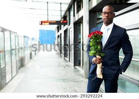 Young African American Businessman Standing at the Metro with Holding a Bouquet of Rose Flowers and Looking at the Camera. - stock photo