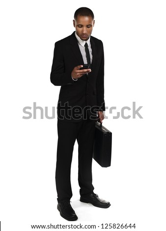 Young African American businessman  text messaging against white background - stock photo