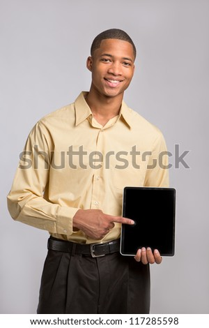 Young African American Businessman Texting on Tablet PC Pad on Grey Background - stock photo