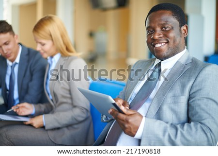 Young African-american businessman with digital tablet looking at camera in airport with two co-workers on background - stock photo