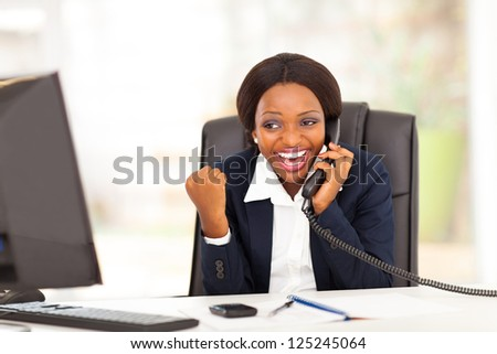 young african american businesswoman receiving exciting news in office - stock photo