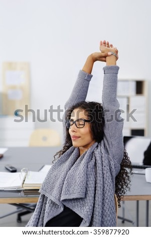 Young African American businesswoman stretching her arms in the air to relieve tension and stress with a look of peaceful bliss - stock photo