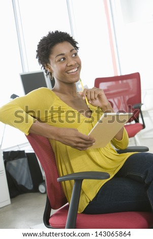 Young African American businesswoman with notepad and pencil sitting on office chair - stock photo