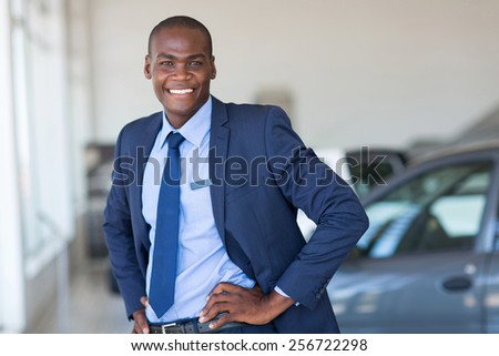 young african american car dealership principal standing in vehicle showroom - stock photo