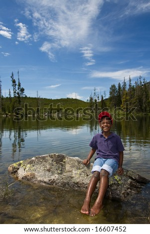 Young African American child playing in a lake at Yellowstone National Park in Wyoming, USA.