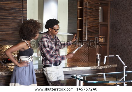 Young African American couple in new furnished Kitchen choosing materials - stock photo
