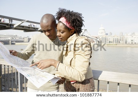 Young african american couple near London's St. Paul's Cathedral, looking at a map.