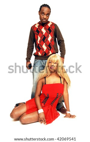 Young African American couple, she is sitting on the floor and he is standing behind her for white background. - stock photo