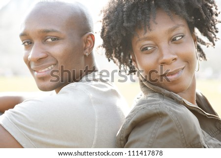 Young african american couple sitting back to back while visiting London on vacation, smiling at camera. - stock photo