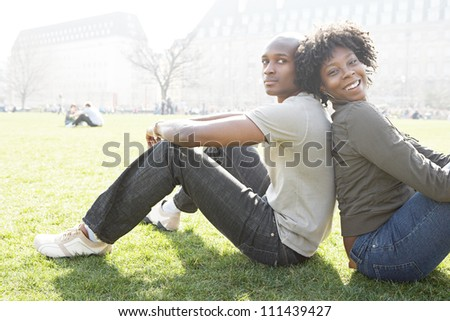 Young african american couple sitting back to back while visiting London on vacation, smiling at camera.