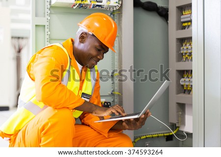 young african american engineer using laptop in machine control room - stock photo
