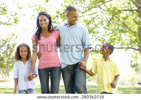 Young African American Family Enjoying Walk In Park - stock photo