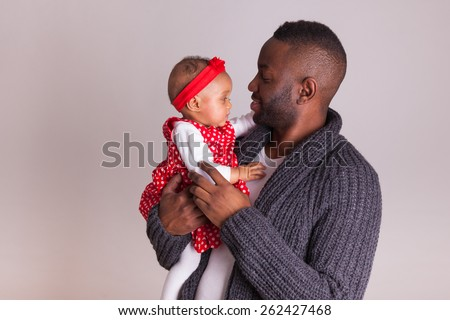 Young african american father holding with her baby girl - stock photo