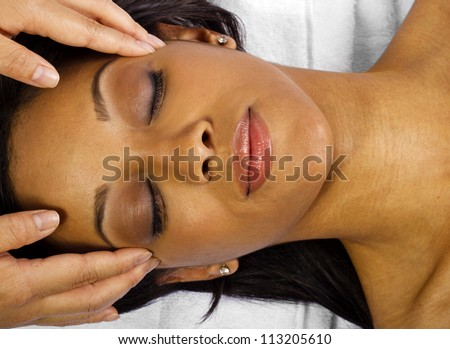 Young African American female getting a facial/head massage - stock photo