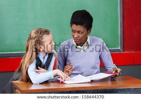 Young African American female teacher looking at schoolgirl in classroom - stock photo