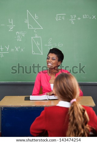 Young African American female teacher looking away with female student in foreground at classroom - stock photo