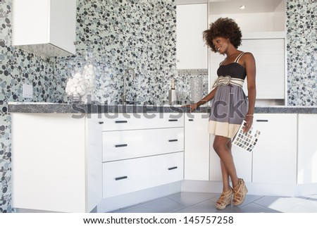 Young African American girl in new furnished Kitchen choosing materials - stock photo