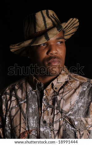 young African American hunter in a safari hat and camo shirt - stock photo